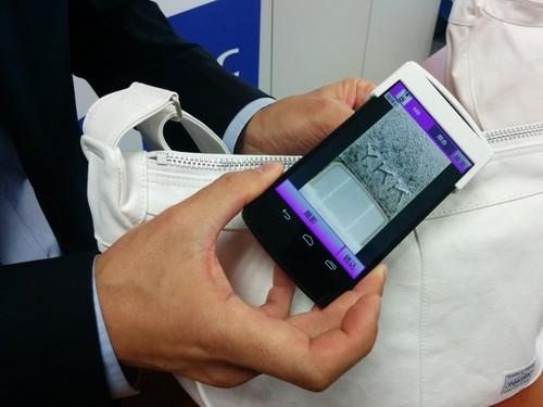 "An NEC staffer demonstrates an anti-counterfeiting smartphone app on Monday in Tokyo. The ""object fingerprint"" technology can compare smartphone photos of minute manufacturing patterns in metal and plastic objects and compare them with a database to establish their origins and authenticity."