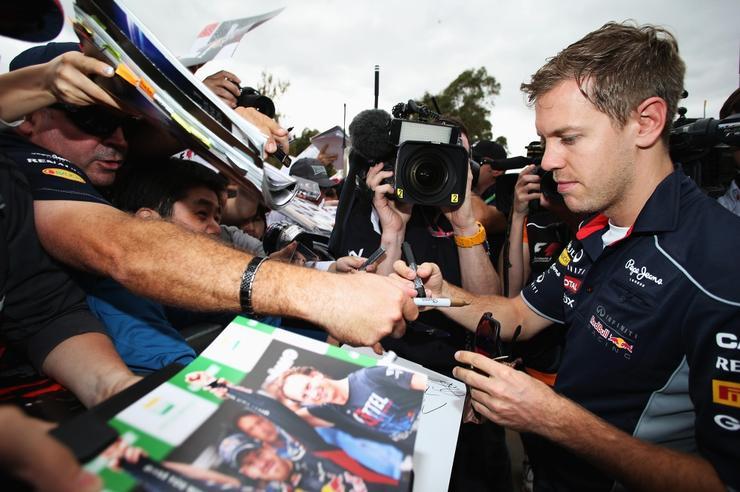 Driver Sebastian Vettel signing autographs for fans